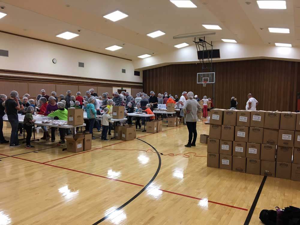 Volunteers in a gymnasium packing meals