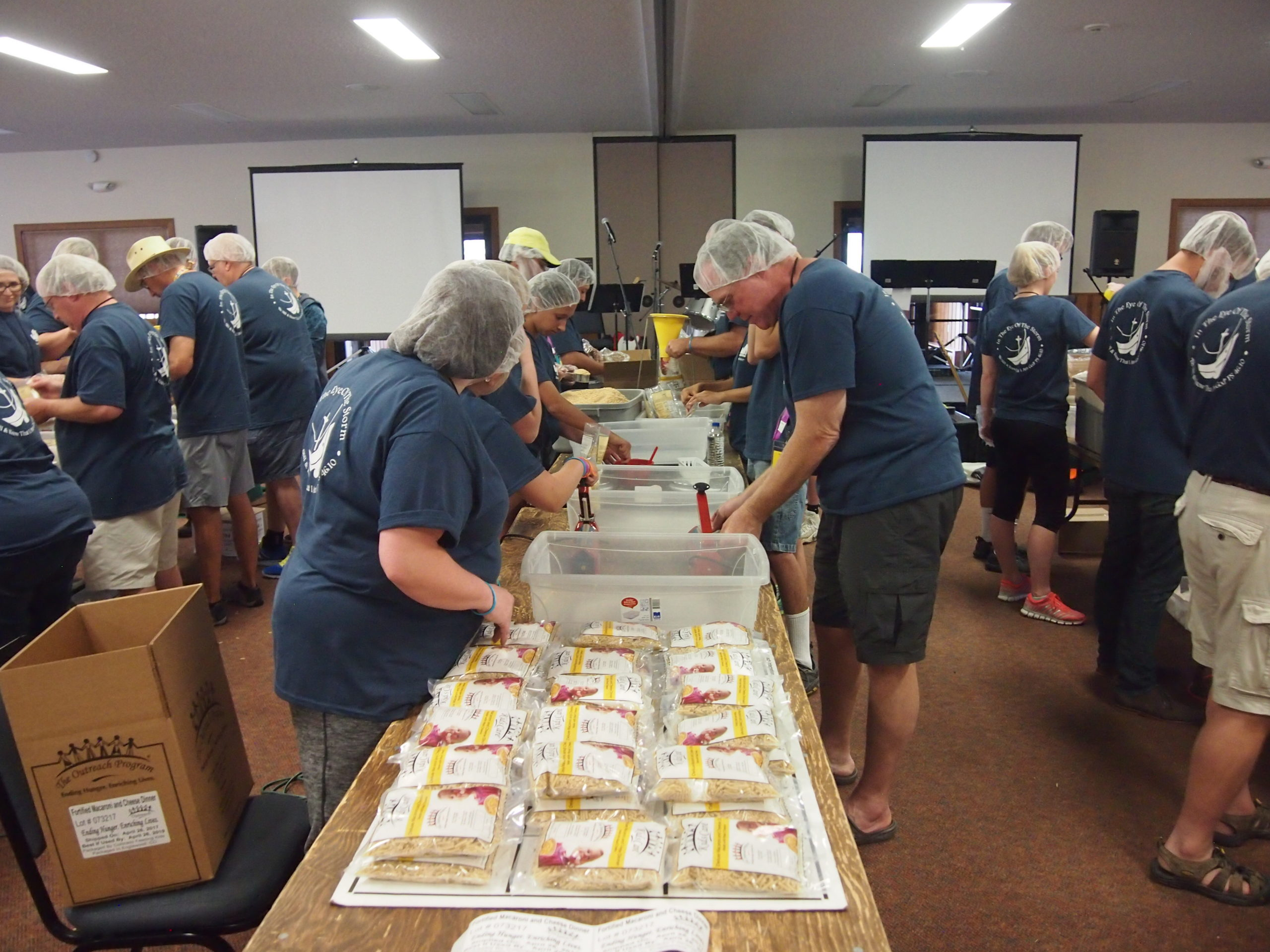 A group of volunteers packing meals and wearing hair nets