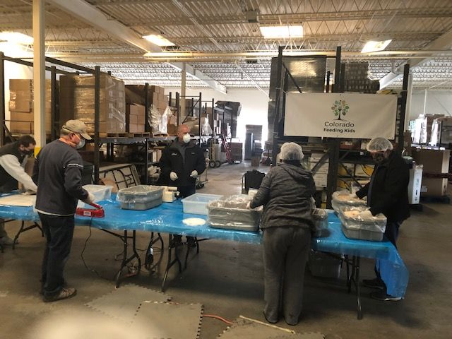 A group of volunteers packing meals and wearing hair nets and masks
